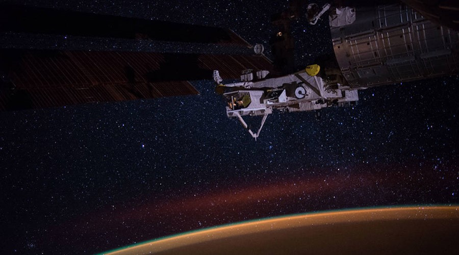 Earth's atmospheric glow, the stars of the Milky Way and an experiment facility at the tip of Japan's Kibo lab module are seen in this night time photograph taken during Expedition 49.